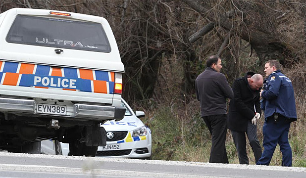 Police don latex gloves as they wait for a body to be recovered from the Shotover River, near Queenstown.