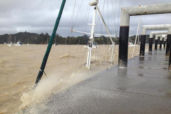 A boat lies submerged at its pier in Opua.