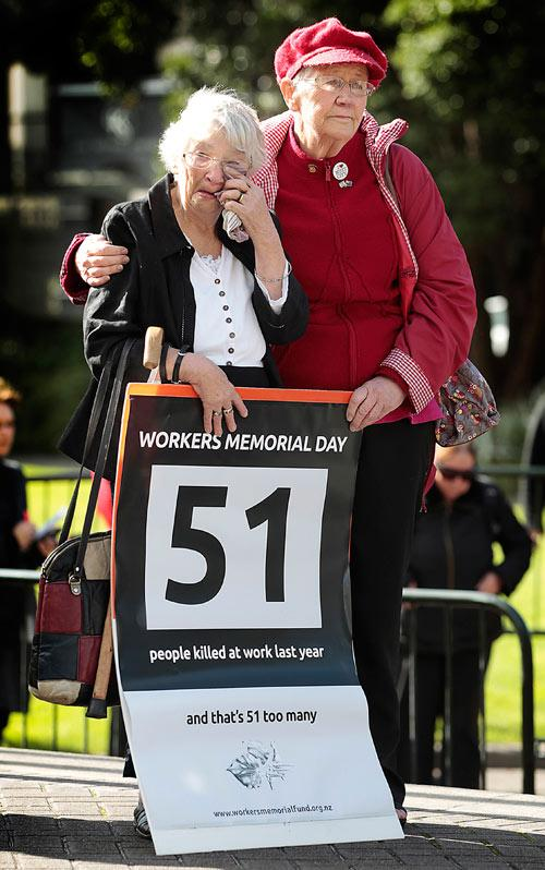 (L-R) Ngaire Lambourne is comforted by Evelyn Richter during a Workers Memorial day which was marked by a funeral procession from the railway station to parliament, Wellington.