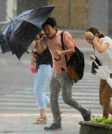 WELLINGTONESQUE: People holding umbrellas walk against strong winds and heavy rain brought about by Typhoon Neoguri in Okinawa on Wednesday.