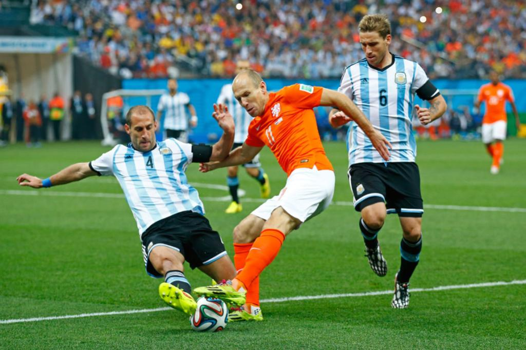 Argentina's Pablo Zabaleta dives in with a challenge on Arjen Robben.