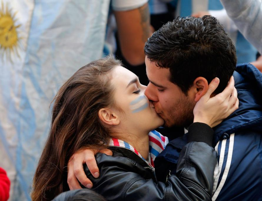 Two Argentina fans find a loving way to pass the time while waiting for the start of the semifinal.