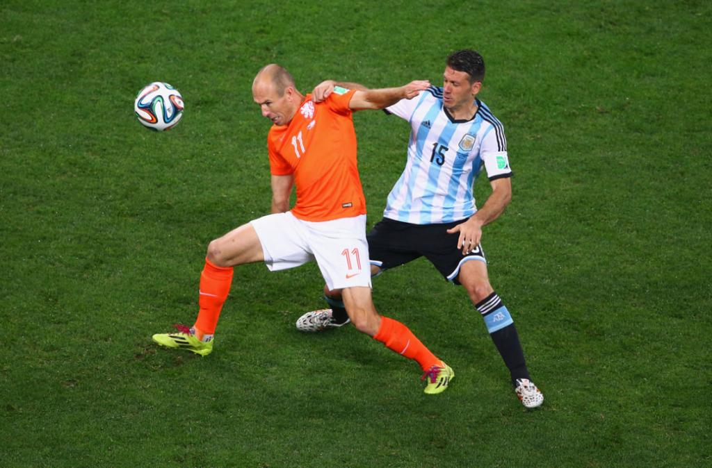 Arjen Robben up to his old tricks, goes to ground after this challenge from Argentina's Martin Demichelis.