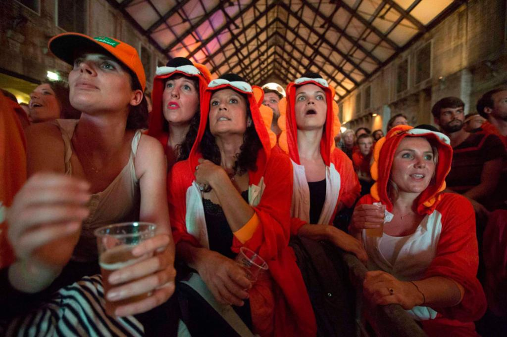 Football fans gather at a public screening in Amsterdam to cheer on Netherlands.