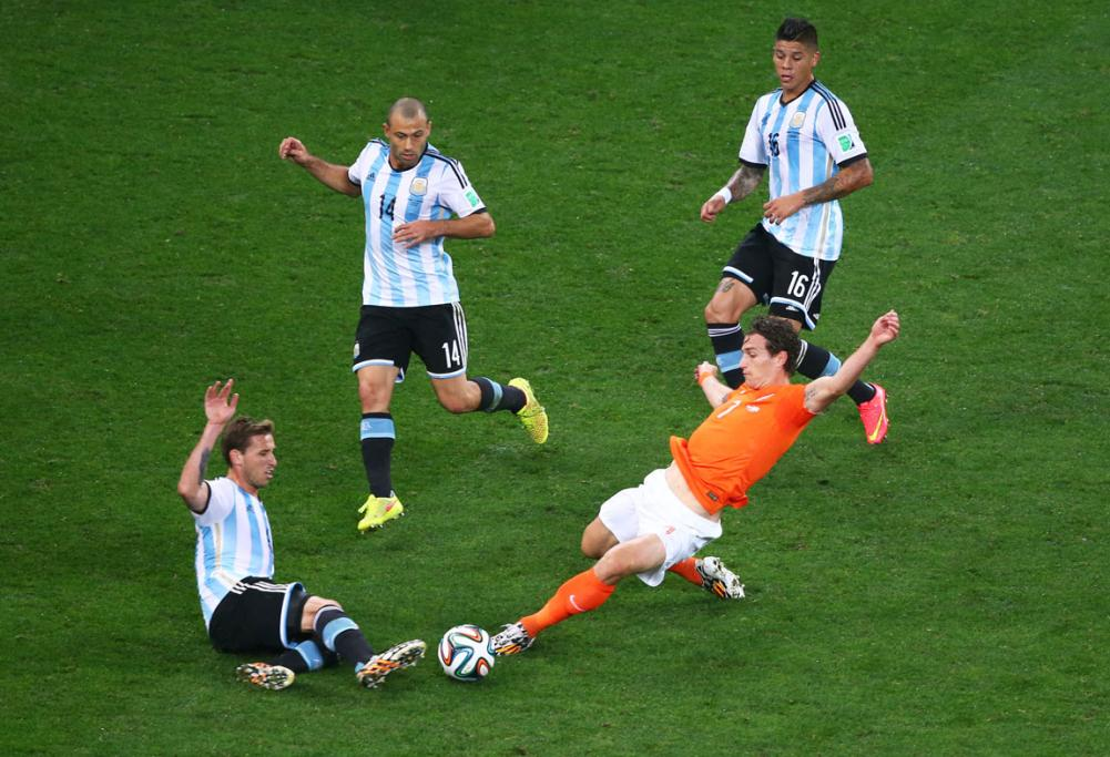 Slippery conditions led to this heavy sliding collision between Lucas Biglia of Argentina and Daryl Janmaat of Netherlands.