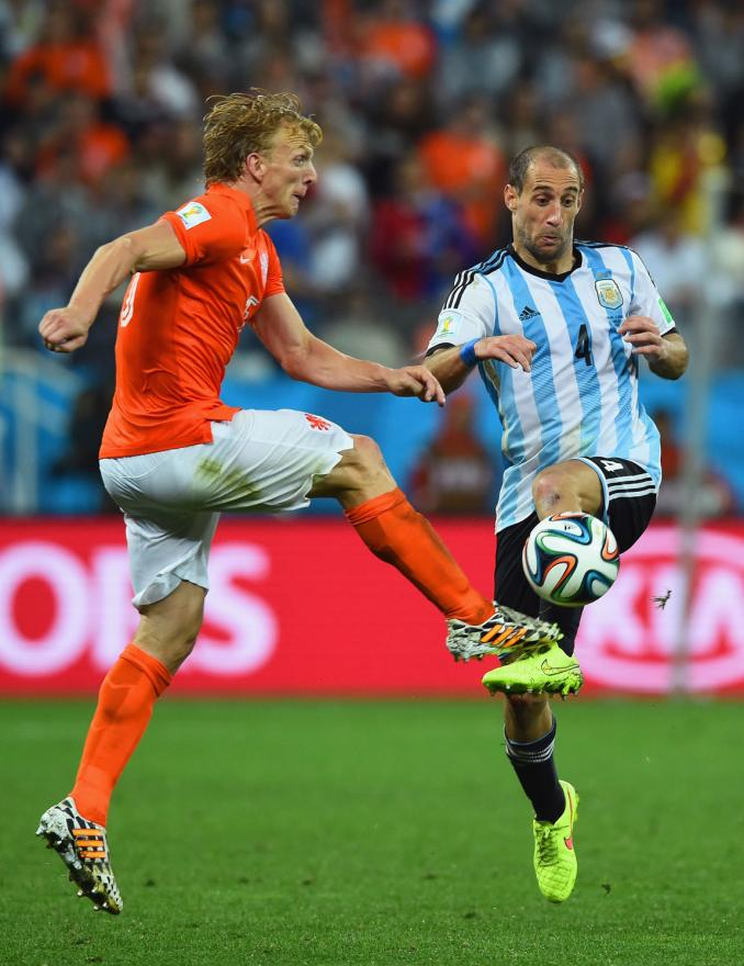 Dirk Kuyt of the Netherlands and Pablo Zabaleta of Argentina go into a heavy aerial collision.