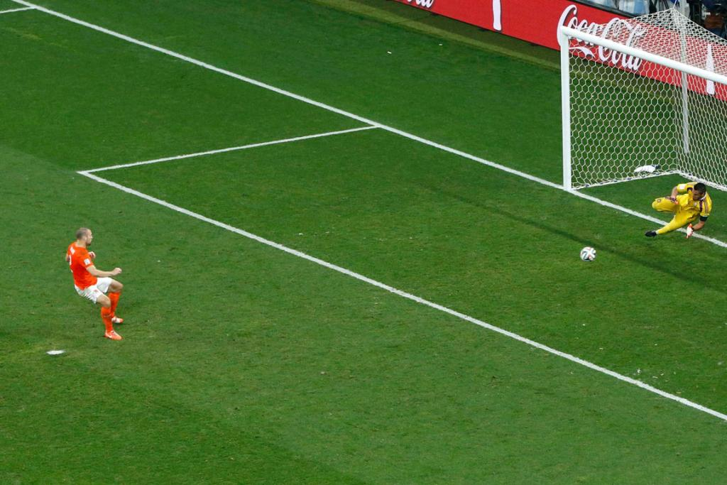Argentina goalkeeper Sergio Romero saves the first Netherlands penalty kick from Ron Vlaar.