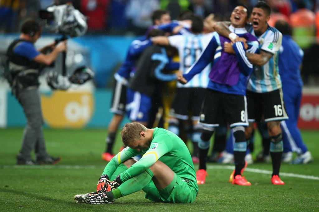Netherlands goalkeeper Jasper Cillessen mourns their loss as Argentina celebrate behind him. He missed all four of Argentina's penalty shots on goal.