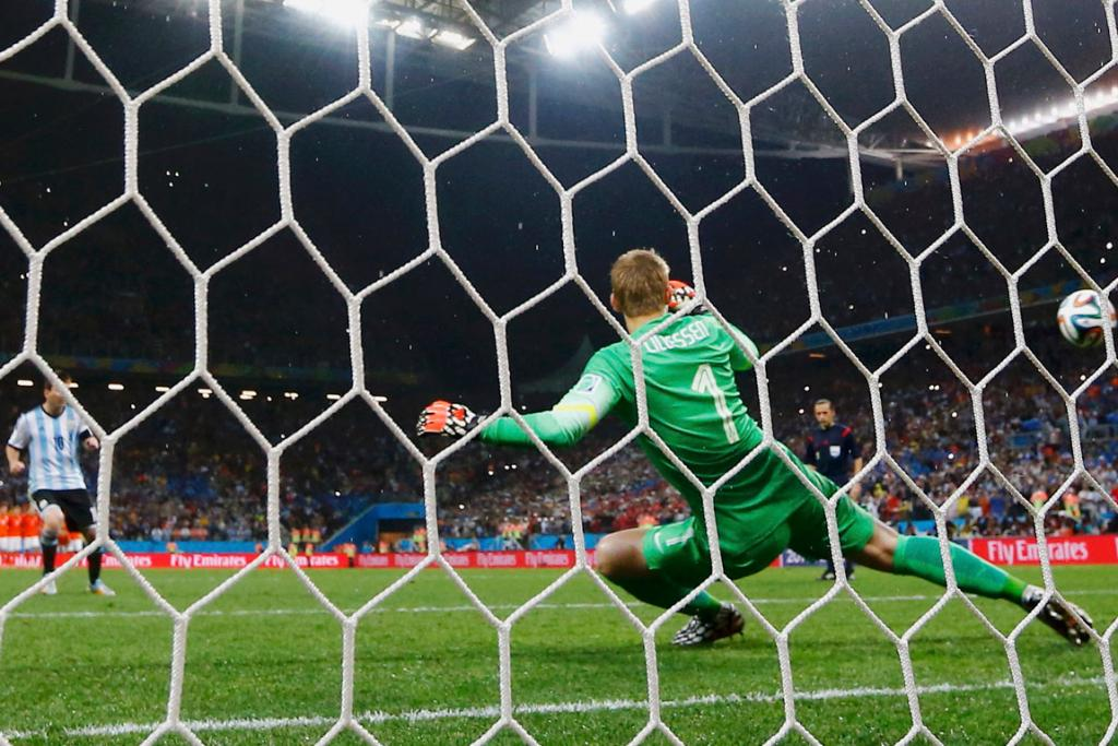 Lionel Messi of Argentina shoots and scores past Jasper Cillessen of the Netherlands.