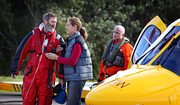 DRY LAND: Scott Donaldson walks from the rescue helicopter to an ambulance, with the support of his wife Sarah.