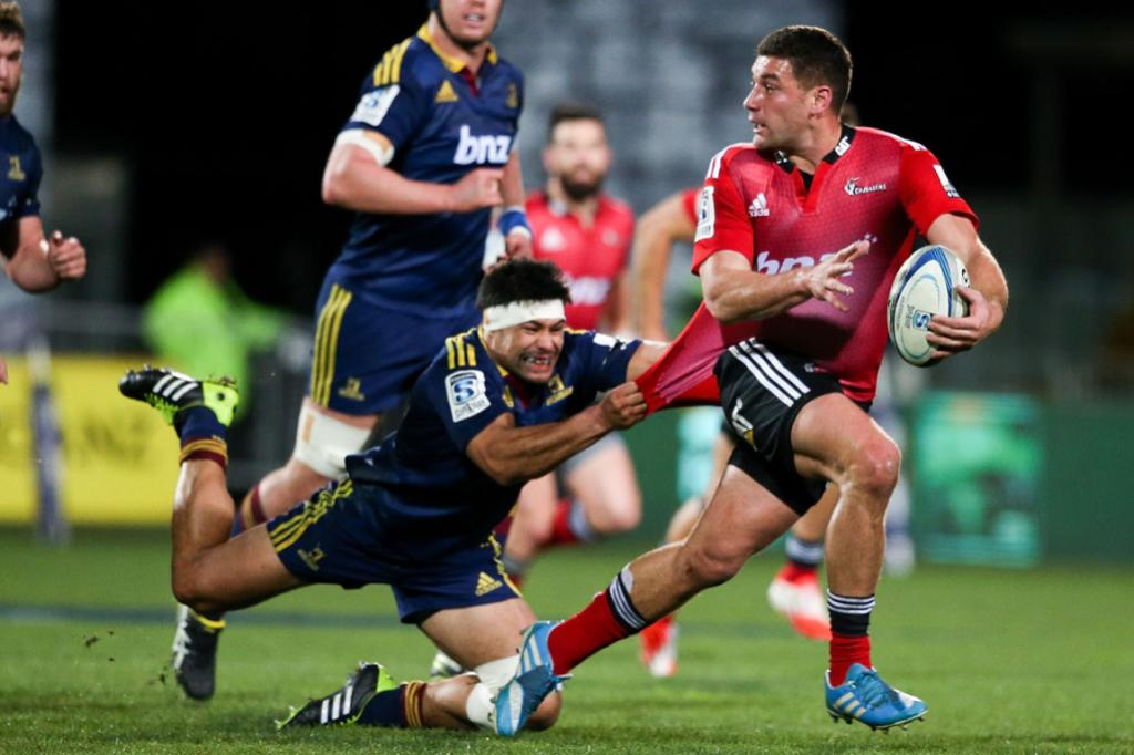 Shane Christie holds on for all money as he tries to bring down Kieron Fonotia in a tackle in the Highlanders' round 19 match against the Crusaders.