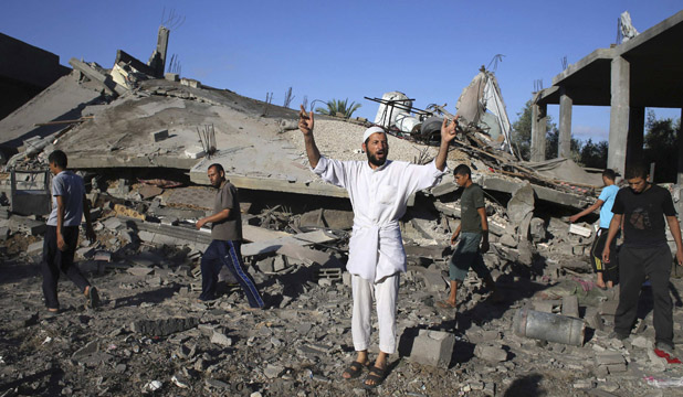 Palestinian man gestures near house destroyed by Israel strikes against Hamas