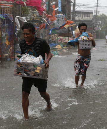 TYPHOON TORMENT: Residents evacuate with belongings as Typhoon Rammasun hits Imus, southwest of Manila.