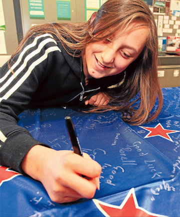 GOOD LUCK: Talia Craddock, 12, signs a New Zealand flag at Blenheim Countdown to wish the Commonwealth Games team well.