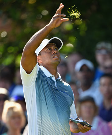 TESTING TIMES: Tiger Woods tosses grass in the air to test the wind before playing a shot on the fifth hole during the first round of the British Open.
