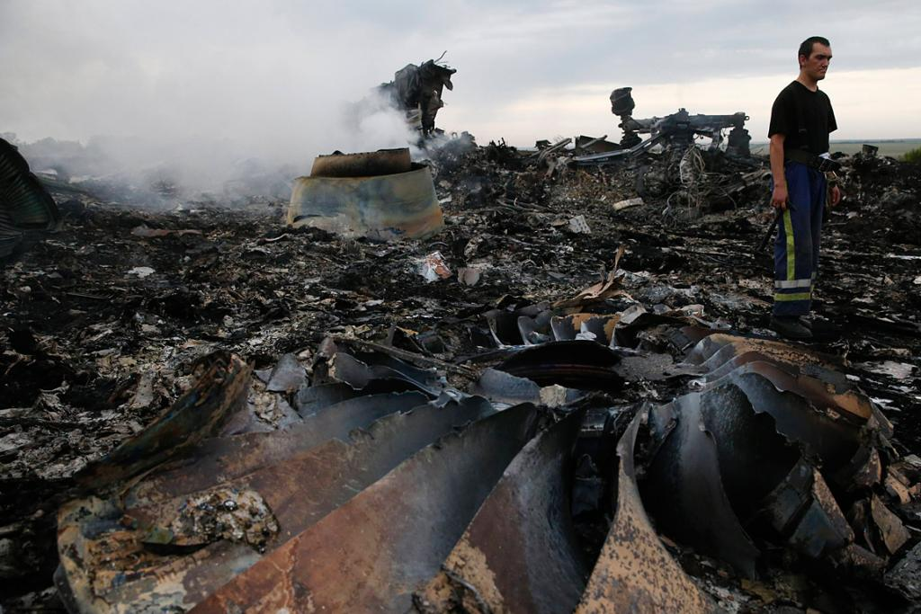 An Emergencies Ministry member walks at the site of the Malaysia Airlines Boeing 777 plane crash in Ukraine.