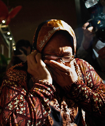 GRIEF: A family member cries as she receives the news of the ill fated flight MH17.