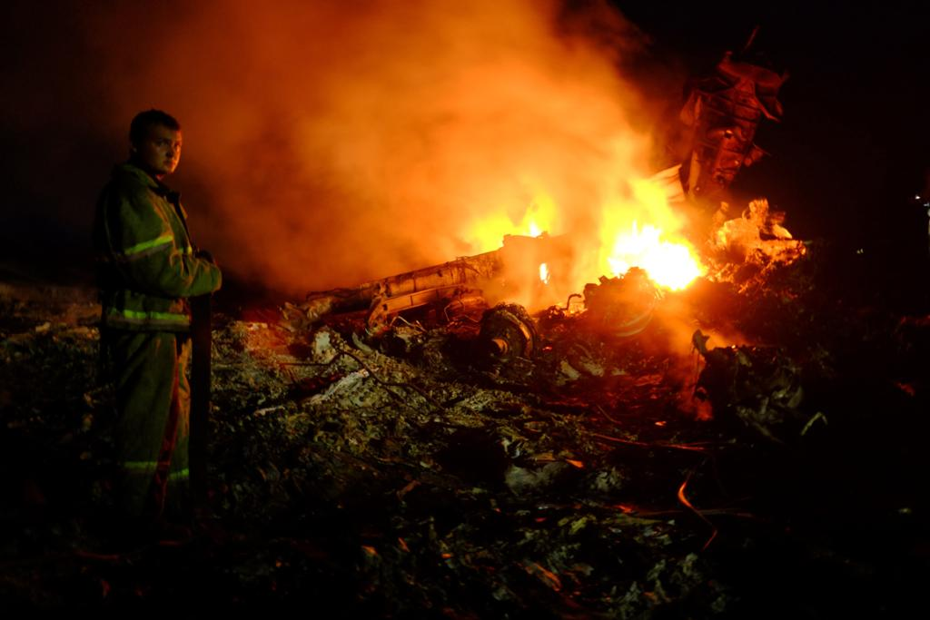 A firefighter stands as flames burst amongst the wreckages of the MH17.
