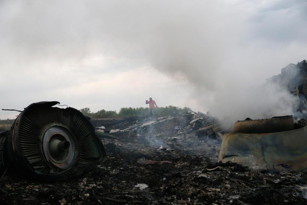 The wreckage smoulders at the site of the MH17 crash.