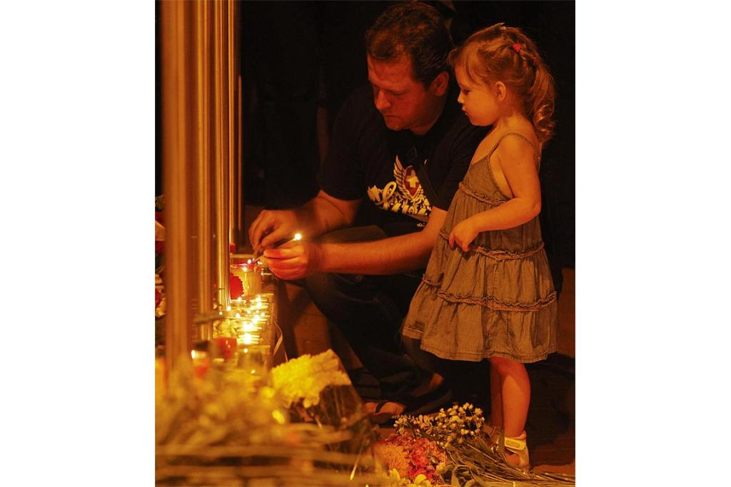 A father and daughter light candles at the Dutch embassy to commemorate the victims of Malaysia Airlines MH17.