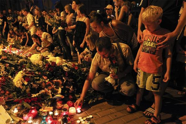 People place candles and flowers at the Dutch embassy for victims of Malaysia Airlines MH17.