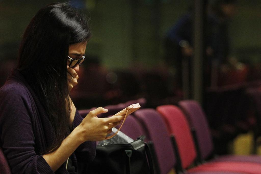 A Malaysian woman who had a relative on board the Malaysian Airlines MH17 reacts to messages on her mobile phone as she waits to travel to Kuala Lumpur.