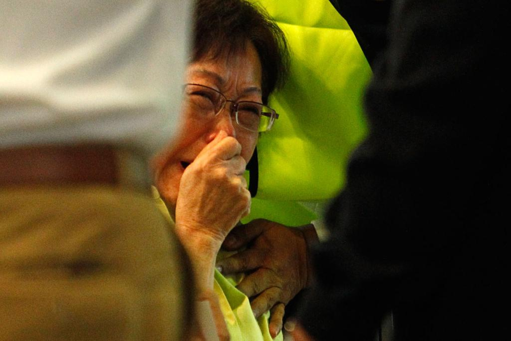 Malaysian Siti Dina weeps after seeing her daughter's name on the list of passengers on board MH17.