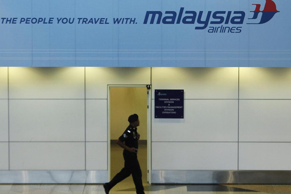 A security officer passes a Malaysia Airlines advertisement at the Kuala Lumpur International Airport in Sepang