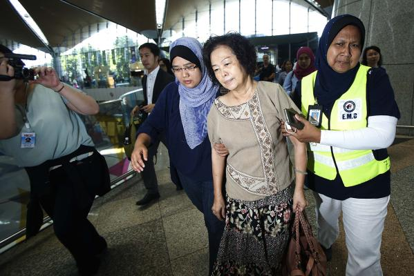 A relative of a passenger onboard the Malaysia Airlines (MAS) MH17 is assisted by MAS staff members as she leaves Kuala Lumpur International Airport.