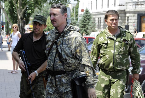 "MH17 PRIME SUSPECT: Self-proclaimed Minister of Defence of  ""Donetsk People's Republic"", Igor Girkin, centre, walks with his bodyguards in the eastern Ukrainian city earlier this month."