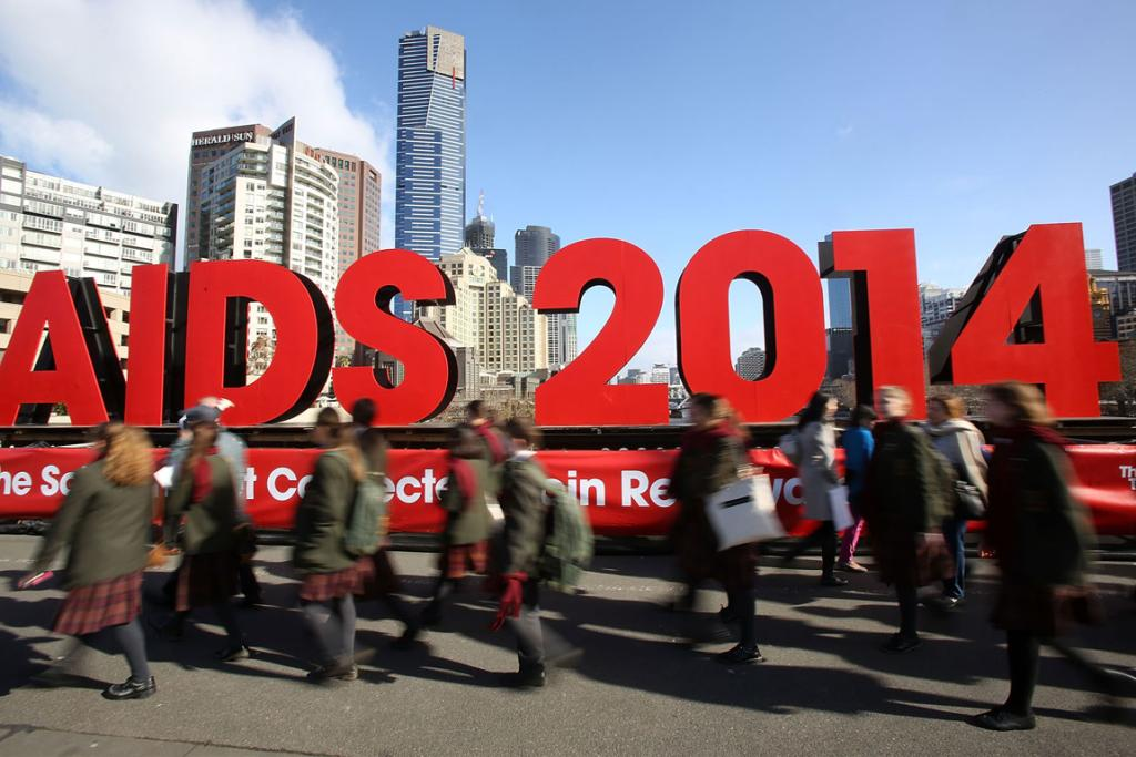 Members of the public walk past signage on the Princes Bridge for the 20th International AIDS Conference in Melbourne, Australia. Twenty-seven Australians and more than 100 AIDS activists, researchers, health workers and delegates bound for the major conference were among those aboard MH17.