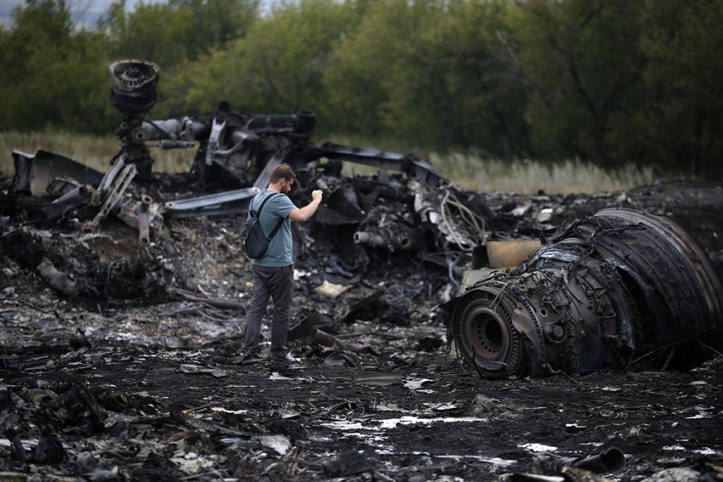 A journalist takes photographs at the site of Thursday's Malaysia Airlines Boeing 777 plane crash.