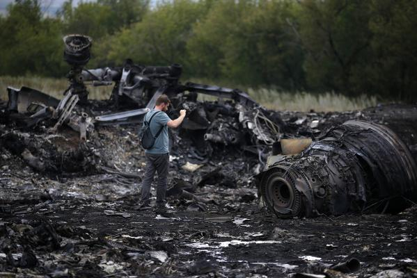 A journalist takes photographs at the site of Thursday's Malaysia Airlines Boeing 777 plane crash