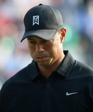 BAD DAY: Tiger Woods walks off the 18th green after a five-over round of 77, which saw him just qualify for the weekend at the British Open on the cut-line.