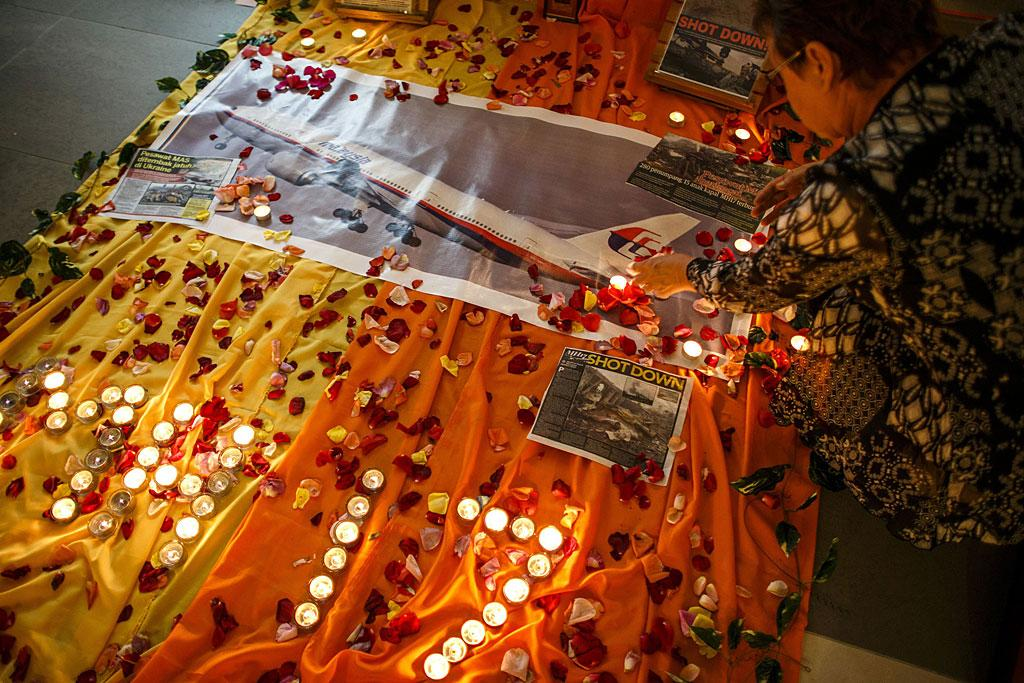A woman lights candles at a memorial for victims of the downed Malaysia Airlines Flight MH17 in Kuala Lumpur.
