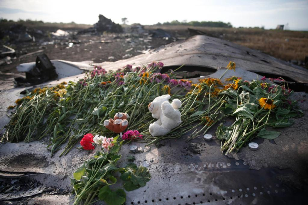 Flowers and mementos lie on wreckage at the crash site of MH17, near the Ukraine settlement of Grabovo.
