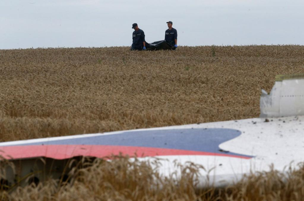 Members of the Ukrainian Emergency Ministry carry a body near the wreckage at the crash site of MH17, near the settlement of Grabovo.