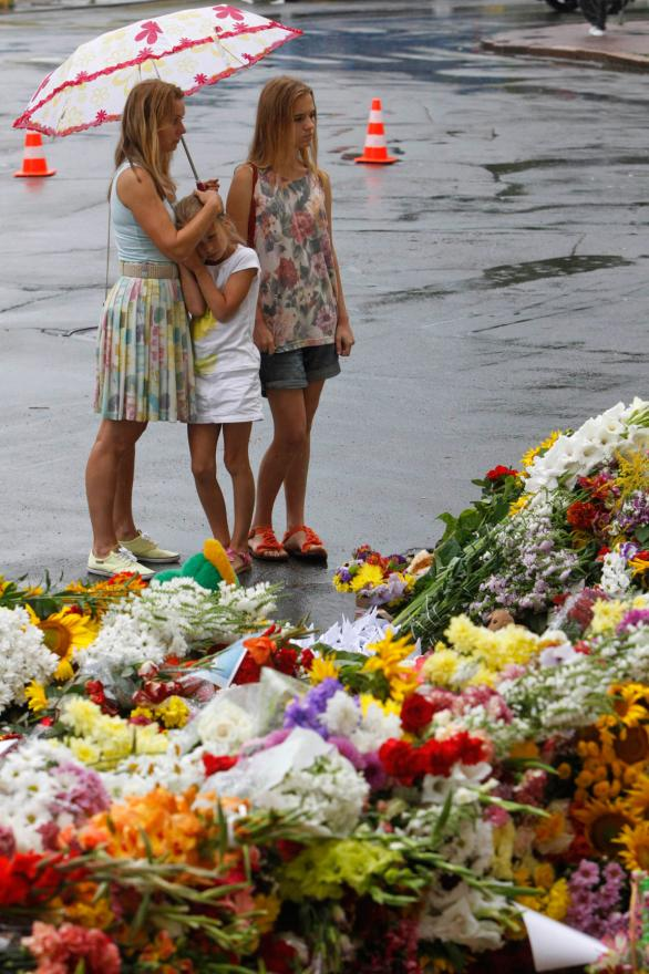 People look at flowers and messages left by local residents for MH17 crash victims outside the Dutch embassy in Kiev, Ukraine.