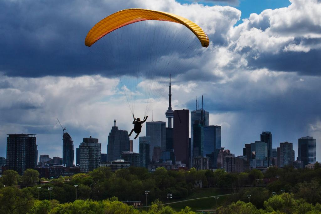 A man paraglides in front of the skyline in Toronto.
