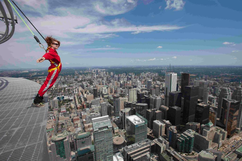 "A reporter leans over the edge of the catwalk during the media preview for the ""EdgeWalk"" on the CN Tower."