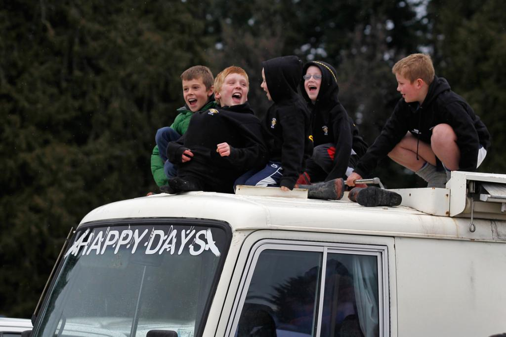 Boys watching the rugby match between Mackenzie and Harlequins at Fairlie from the top of a bus.