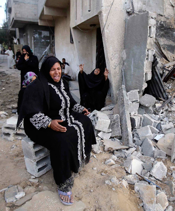 SHELLED: Palestinian women next to the rubble of their relatives' house, which police said was destroyed in an Israeli air strike.