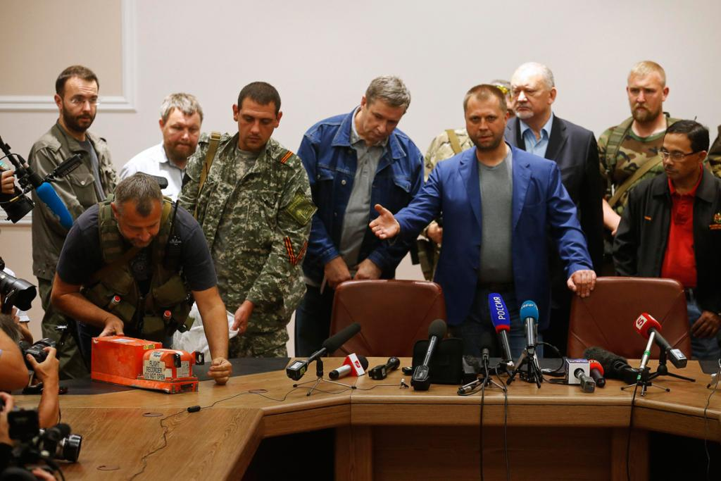 Senior Ukrainian separatist leader Aleksander Borodai gestures as a rebel places the black boxes of Malaysia Airlines flight MH17 on a desk.