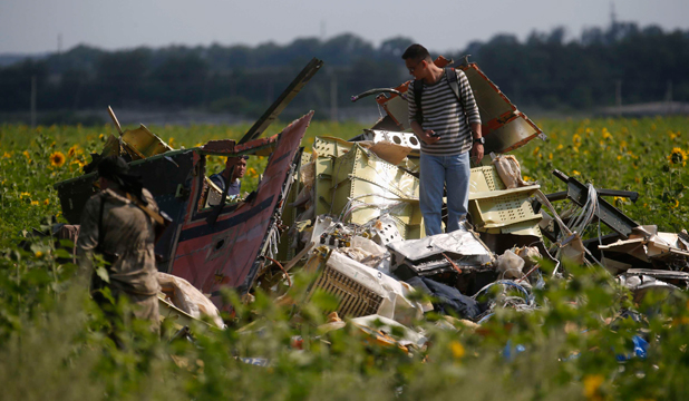 TAMPERED WITH?: A Malaysian air crash investigator inspects the wreckage of Malaysia Airlines Flight MH17.
