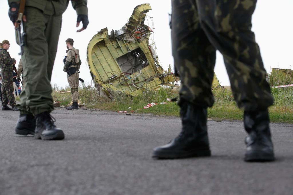 Armed pro-Russian separatists watch as monitors from the Organization for Security and Cooperation in Europe and Malaysian air crash investigators inspect the crash site.