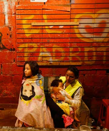 Evicted residents of Tower of David wait for a bus to transport them to their new house in Caracas on Tuesday.
