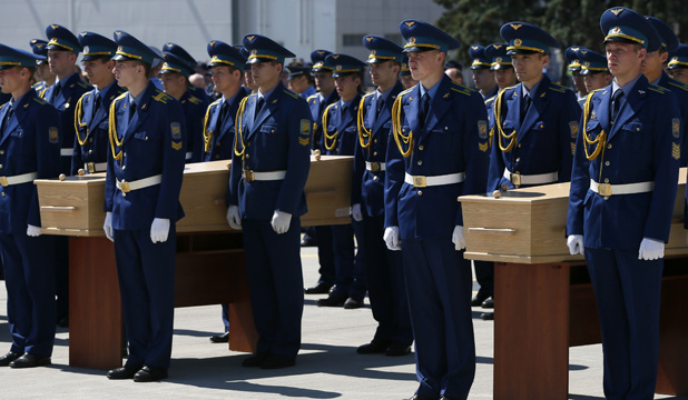 FAREWELL: A Ukrainian guard of honour stood by some of the coffins of victims of Flight MH17 before they were loaded on to a plane at Kharkiv airport.