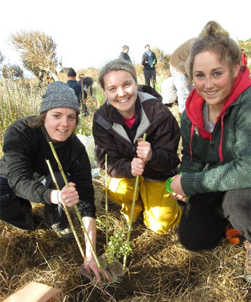 DIGGING IN: University of Otago environmental management year two students Alice Thomson and Lucy Underwood and Southern Institute of Technology environmental management year one student Kate Dunlevey learn new skills to protect native trees while planting at Te Rere private scientific reserve on the Catlins coast at the weekend.