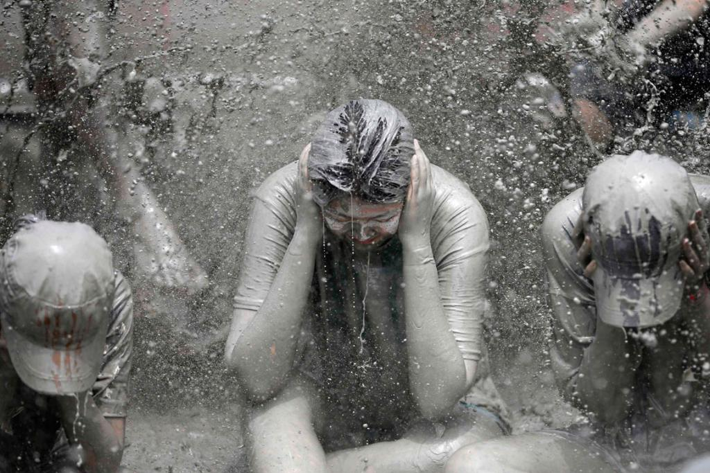 Tourists play in the mud during the Boryeong Mud Festival at Daecheon beach in Boryeong.