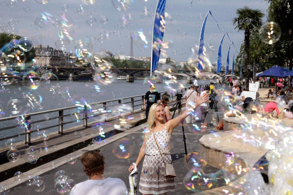 "A woman reacts to bubble machines as ""Paris Plage"" (Paris Beach) opens along the banks of River Seine in Paris."